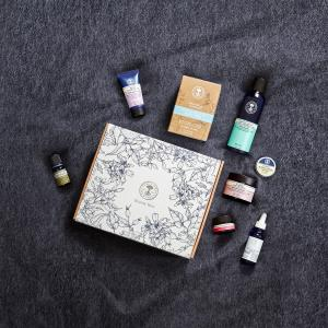 Dark grey blanket scattered with beauty products