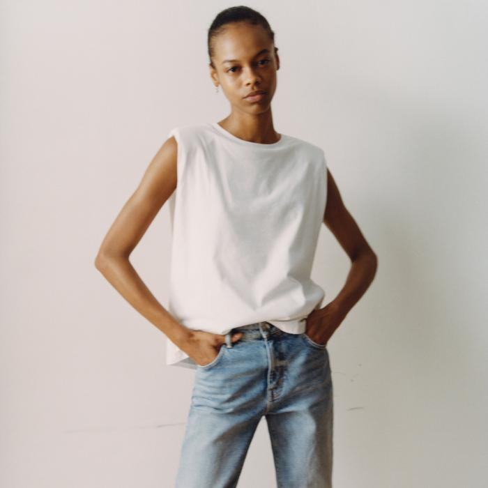 Model wearing a an All Saints white tank top and blue jeans
